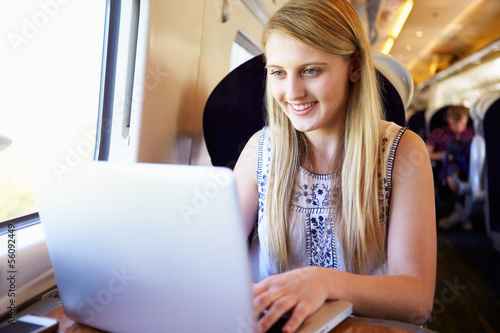 Teenage Girl Using Laptop On Train Journey
