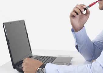 using electric cigarette and laptop
