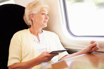 Senior Woman Reading E Book On Train Journey