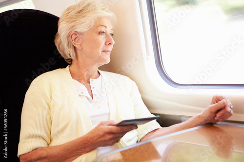 Senior Woman Reading E Book On Train Journey