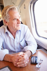 Senior Man Relaxing On Train Journey