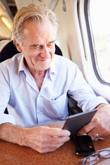 Senior Man Reading E Book On Train Journey