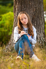 Teen-girl writing in a notebook while sitting in the park