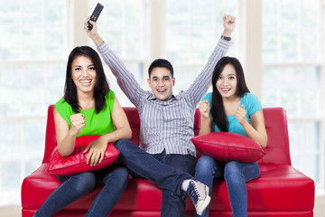 Happy young teenager watching tv at home