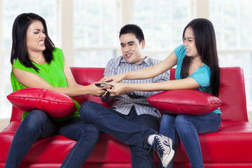 Three asian teenager fighting for a remote