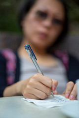 Close-up of a Chines woman writing a letter on a table.