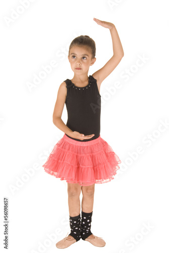 cute ballerina girl posing in dance position in pink tutu