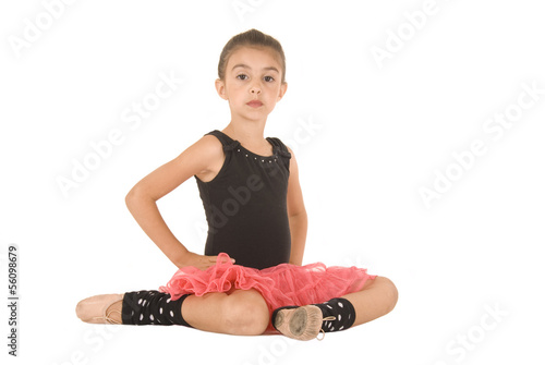Beautiful young ballerina sitting in pink tutu and black leotard