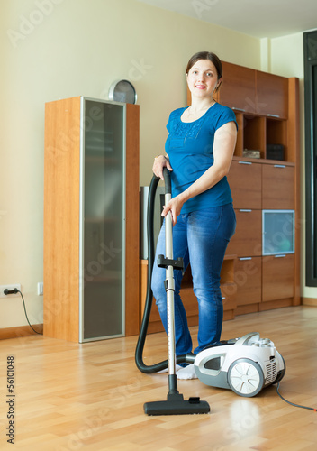 Woman cleans with vacuum cleaner