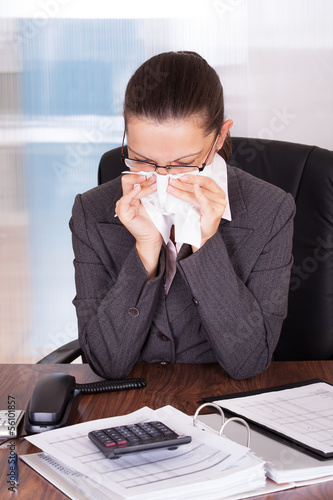 Sick young businesswoman blowing her nose