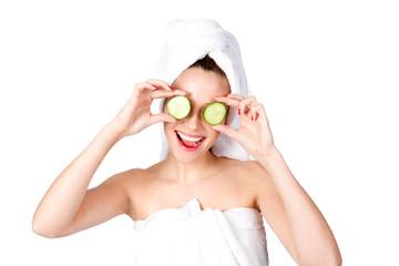 Lachende junge Frau mit Gurken vor den Augen