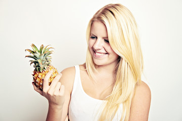 woman is holding a little pineapple