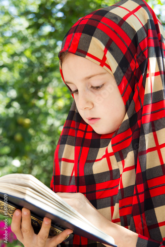Little muslim girl praying - reading holly koran