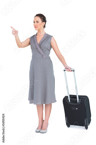 Smiling gorgeous woman carrying her suitcase pointing finger