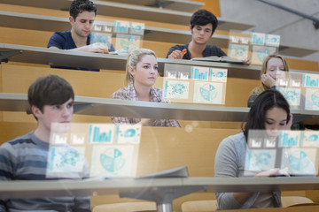 Focused students in lecture hall working on their futuristic tab