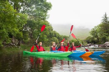 Friends kayaking together cheering at camera