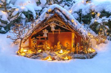 beleuchtete Weihnachtskrippe im Schnee