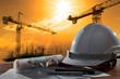 Leinwandbild Motiv safety helmet and architect pland on wood table with sunset scen
