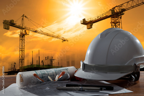 canvas print picture safety helmet and architect pland on wood table with sunset scen