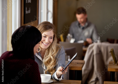 Woman Showing Digital Tablet to Friend