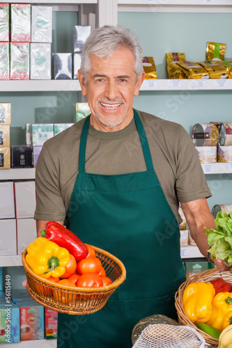 Senior Salesman Holding Vegetable Basket