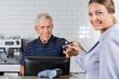 Female Customer Giving Credit Card To Senior Cashier