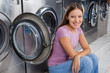 Woman Sitting Against Washing Machines
