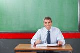 Confident Male Teacher With Pen And Binder Sitting At Desk