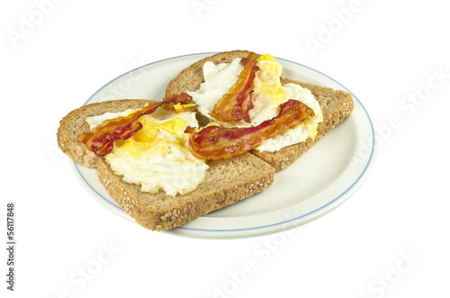 Two slices of brown bread with fried egg and bacon.