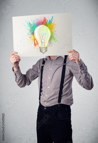 Businessman holding a cardboard with paint splashes and lightbul