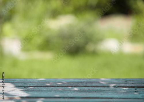 Wooden table against a blurred green background