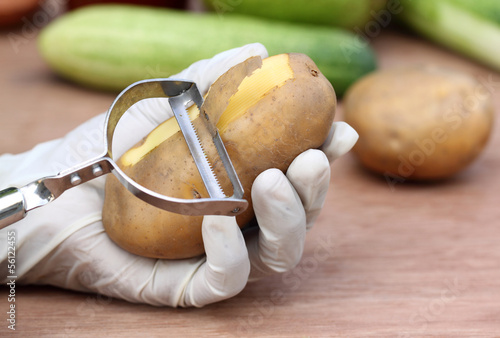 Peeling potato in kitchen