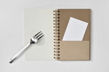 Blank notepad with fork and a piece of paper on white background