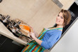 Attractive woman in striped apron slices vegetables