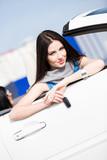 Pretty female driver in a white car showing the car key