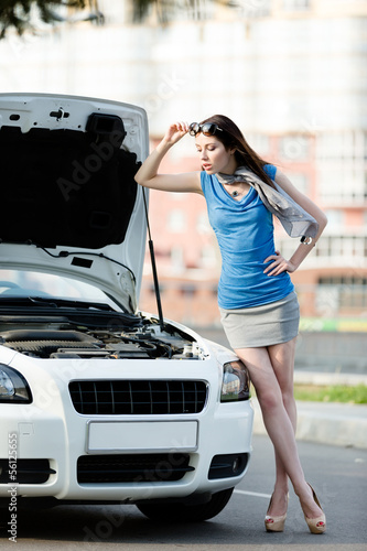 Woman repairing the broken car on the road