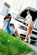 Two pretty girls try to repair the broken car on the road