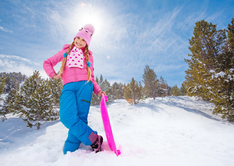 Happy girl in pink standing with sled