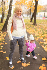 Mother with child in Autumn city street park