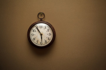 Old retro clock on brown wall
