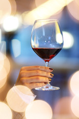 Female hand holding glass of red wine