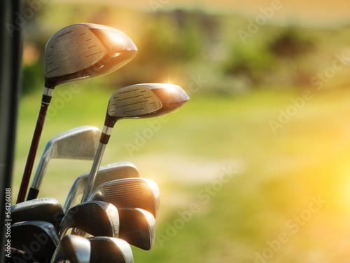 Leinwanddruck Bild Golf clubs drivers over green field background