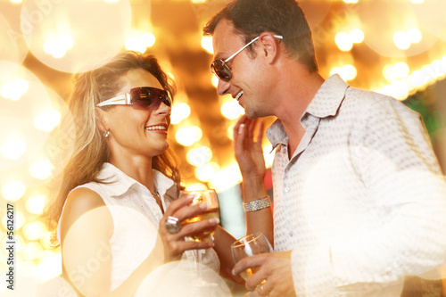 Adult couple enjoying nightlife with glasses of champagne