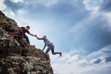 Man giving helping hand to friend to climb mountain rock cliff