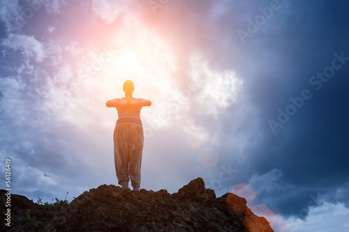 Woman in yoga meditation on top of mountain