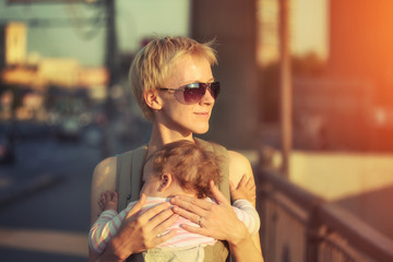 Mother with baby on city street at sunset
