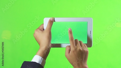 Business hand playing modern tablet computer with green screen