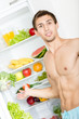 Man stands near the opened fridge which is full of fruit