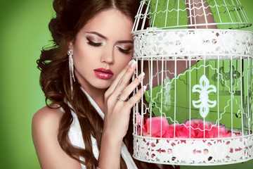Portrait sexy woman with vintage bird cage isolated on green bac