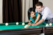 Man teaching girl to play billiards